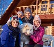 Les amis gais avec le chien passent des vacances d'hiver ensemble au cottage de montagne Images libres de droits