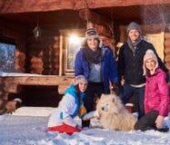Les amis gais avec le chien passent des vacances d'hiver ensemble au cottage de montagne Photos stock