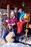 Les amis gais avec le chien passent des vacances d'hiver ensemble au cottage de montagne Images stock