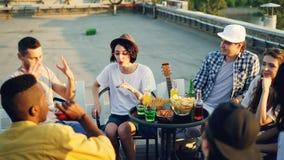 Les amis gais sont causants et buvants de la limonade se reposant sur le dessus de toit le jour ensoleillé chaud avec des casse-c clips vidéos