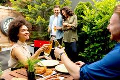Les amis grillant la nourriture et appréciant le barbecue font la fête dehors Images libres de droits