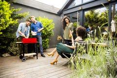 Les amis grillant la nourriture et appréciant le barbecue font la fête dehors Image libre de droits