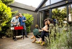 Les amis grillant la nourriture et appréciant le barbecue font la fête dehors Images stock