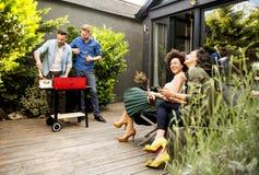 Les amis grillant la nourriture et appréciant le barbecue font la fête dehors Photos stock