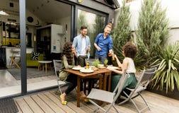 Les amis grillant la nourriture et appréciant le barbecue font la fête dehors Photographie stock libre de droits