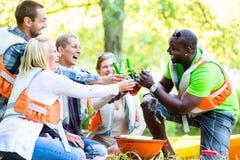 Les amis grillent tout entier après des sports en bière potable de forêt Photo stock