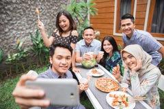 Les amis grillent tout entier au selfie extérieur et prenant ensemble Image libre de droits