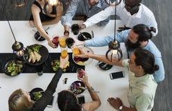 Les amis grillent un verre de jus ensemble dans le restaurant Image libre de droits