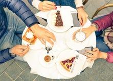 Les amis groupent avec des gâteaux café et lait au restaurant de barre Photographie stock libre de droits