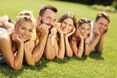 Les amis groupent avoir l'amusement ensemble sur l'herbe Photographie stock
