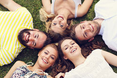 Les amis groupent avoir l'amusement ensemble sur l'herbe Image libre de droits
