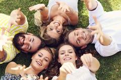 Les amis groupent avoir l'amusement ensemble sur l'herbe Images stock