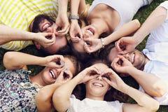 Les amis groupent avoir l'amusement ensemble sur l'herbe Photos stock