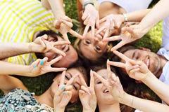 Les amis groupent avoir l'amusement ensemble sur l'herbe Photographie stock libre de droits