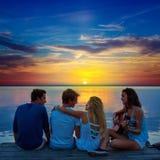 Les amis groupent jouer la guitare dans le pilier de coucher du soleil au crépuscule Photo stock