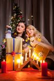 Les amis heureux avec de grands boîte-cadeau dans Noël ont décoré la pièce Photographie stock libre de droits