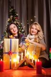 Les amis heureux avec de grands boîte-cadeau dans Noël ont décoré la pièce Photo libre de droits
