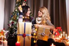 Les amis heureux avec de grands boîte-cadeau dans Noël ont décoré la pièce Image stock