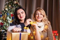 Les amis heureux avec de grands boîte-cadeau dans Noël ont décoré la pièce Image libre de droits