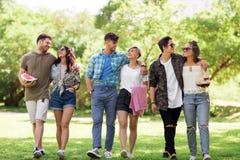 Les amis heureux avec la couverture de pique-nique à l'été se garent Photos libres de droits