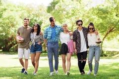 Les amis heureux avec la couverture de pique-nique à l'été se garent Photographie stock