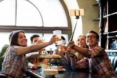 Les amis heureux avec le selfie collent à la barre ou au bar Photographie stock libre de droits