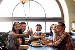 Les amis heureux avec le selfie collent à la barre ou au bar Images stock