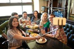 Les amis heureux avec le selfie collent à la barre ou au bar Photos stock