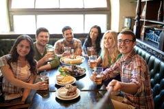 Les amis heureux avec le selfie collent à la barre ou au bar Photo libre de droits