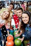 Les amis heureux dans le bowling matraquent à la saison d'hiver Photo libre de droits