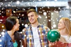 Les amis heureux dans le bowling matraquent à la saison d'hiver Image libre de droits