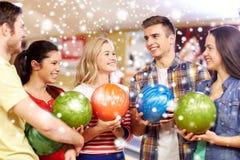 Les amis heureux dans le bowling matraquent à la saison d'hiver Photo stock