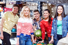 Les amis heureux dans le bowling matraquent à la saison d'hiver Image stock