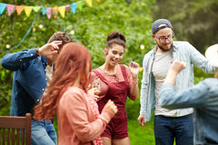 Les amis heureux dansant à l'été font la fête dans le jardin Photos stock