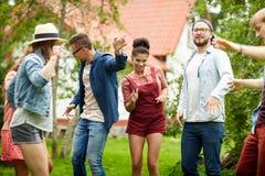 Les amis heureux dansant à l'été font la fête dans le jardin Photographie stock