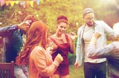Les amis heureux dansant à l'été font la fête dans le jardin Images stock