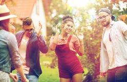 Les amis heureux dansant à l'été font la fête dans le jardin Photographie stock libre de droits