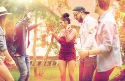 Les amis heureux dansant à l'été font la fête dans le jardin Image stock