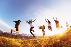 Les amis heureux de groupe court et saute le coucher du soleil de montagnes Photos libres de droits