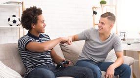 Les amis heureux donnant des poings se cognent tout en jouant le jeu vidéo images stock