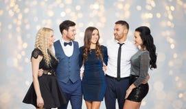 Les amis heureux en partie vêtx étreindre au-dessus des lumières Image libre de droits