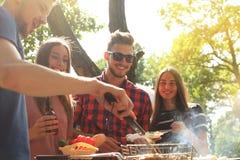 Les amis heureux grillant la viande et appréciant le barbecue font la fête dehors Photo libre de droits