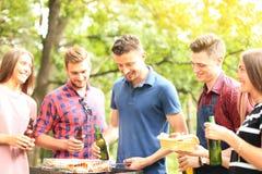 Les amis heureux grillant la viande et appréciant le barbecue font la fête dehors Images libres de droits