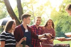 Les amis heureux grillant la viande et appréciant le barbecue font la fête dehors Images stock