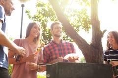 Les amis heureux grillant la viande et appréciant le barbecue font la fête dehors Image libre de droits