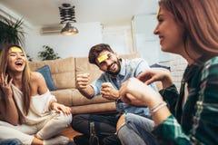 Les amis heureux jouant le jeu devinent qui et ayant l'amusement Photographie stock