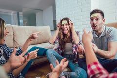 Les amis heureux jouant le jeu devinent qui et ayant l'amusement Images libres de droits