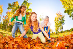 Les amis heureux jouant le rouge part dans la forêt Photographie stock