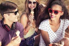 Les amis heureux mangeant le crème Photo libre de droits