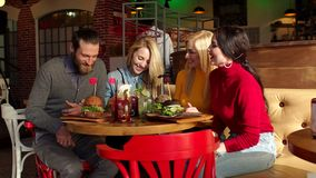 Les amis heureux mangent des hamburgers, parlent et sourient dans un café banque de vidéos